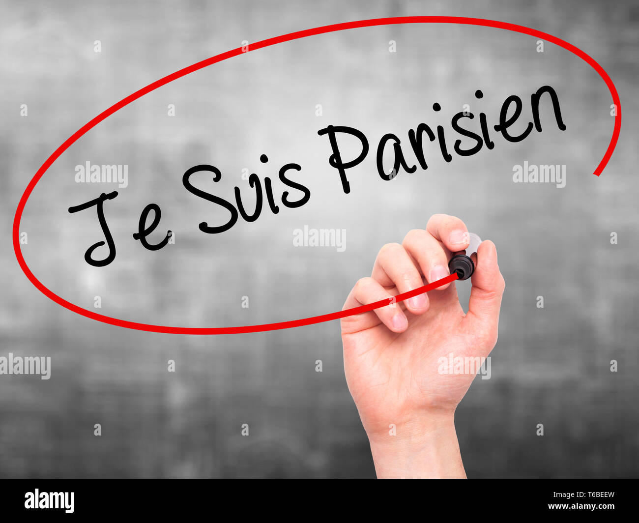Man Hand writing Je Suis Parisien with black marker on visual screen Stock Photo