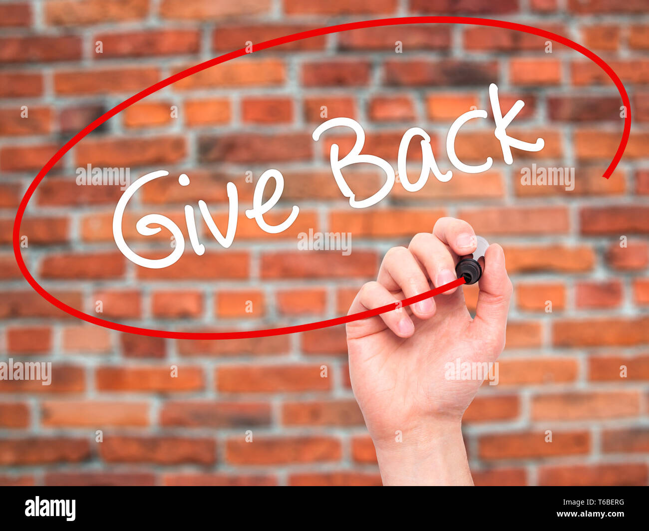 Man Hand writing Give Back with black marker on visual screen - Stock Image