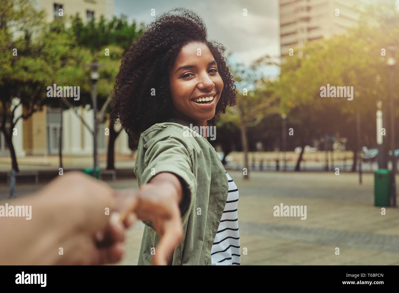 Boyfriend following his happy girlfriend in the city Stock Photo