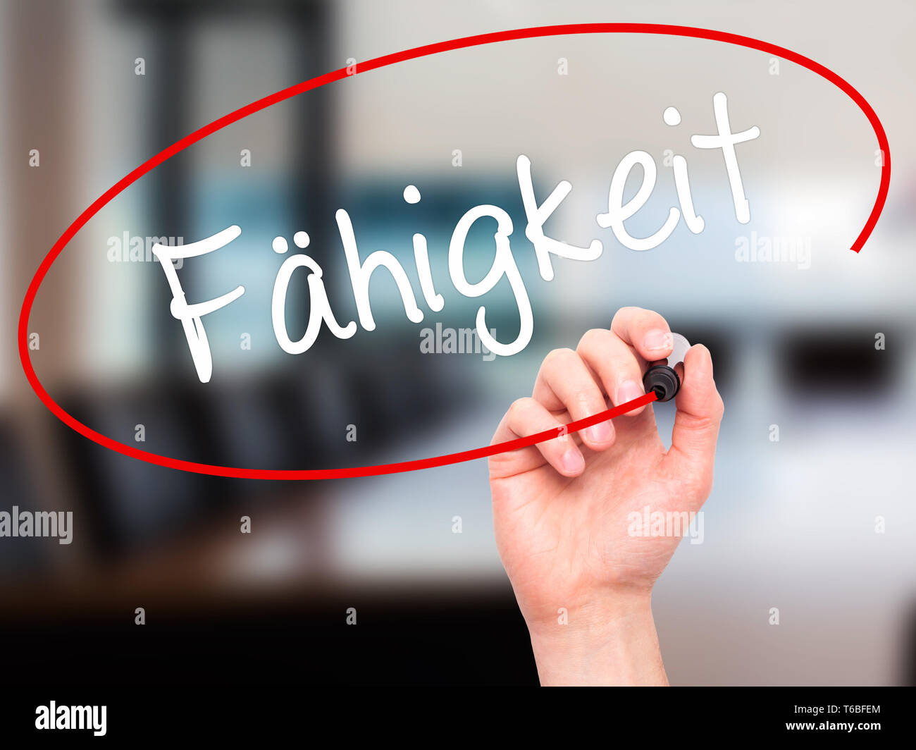 Man Hand writing Fahigkeit (Ability in German) with black marker on visual screen Stock Photo