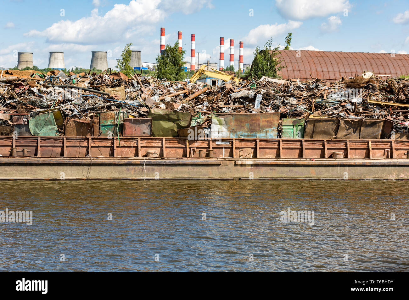 Heap of scrap metal on the river bank - Stock Image