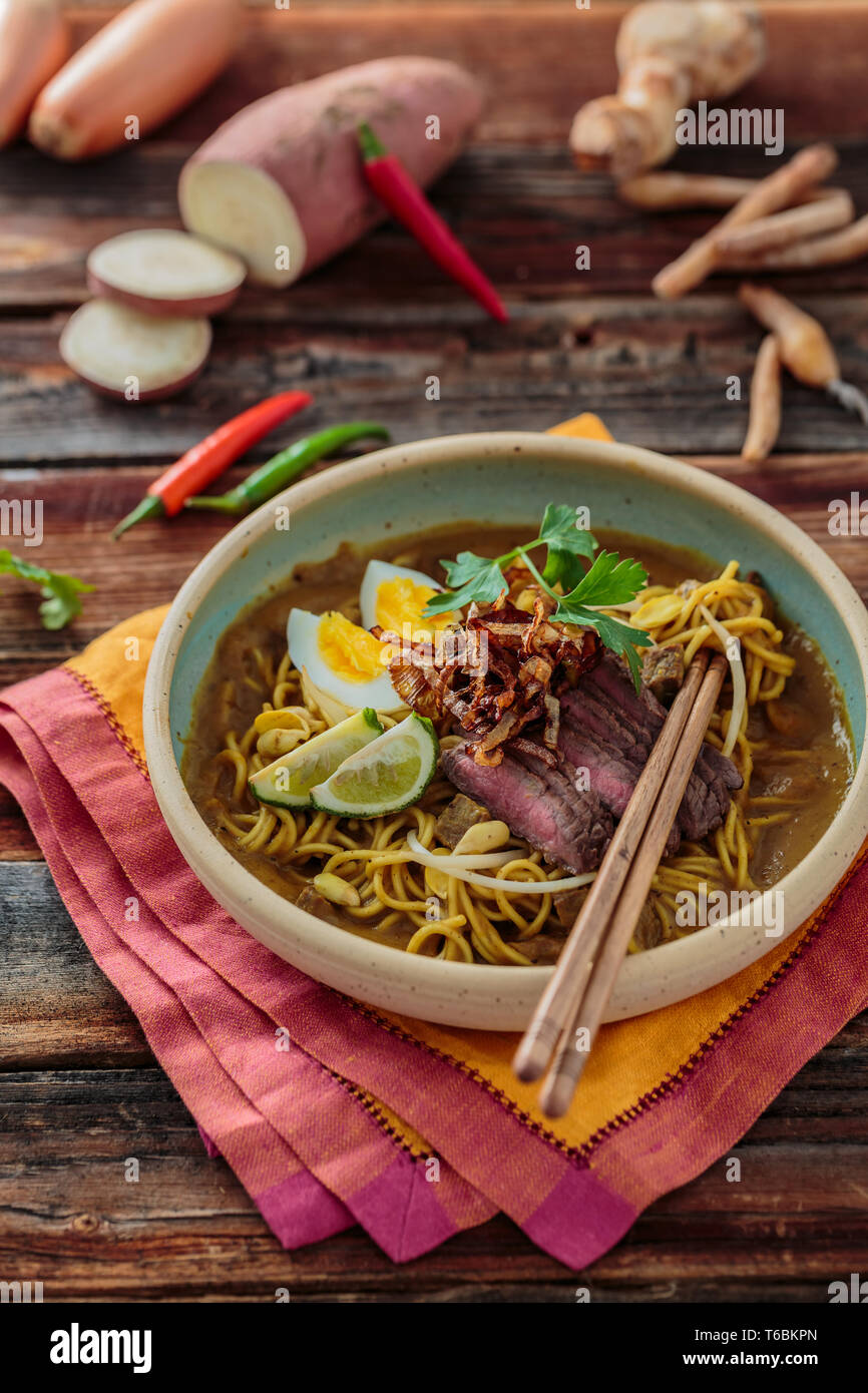 Bowl of spicy mee rebus with chopsticks, malaysian cuisine - Stock Image