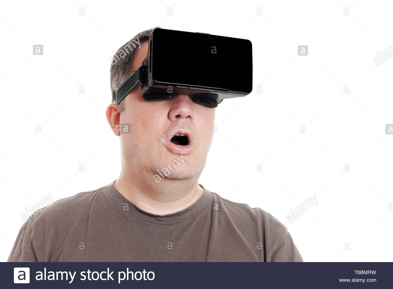 middle aged man wearing VR virtual reality headset is stunned - Stock Image