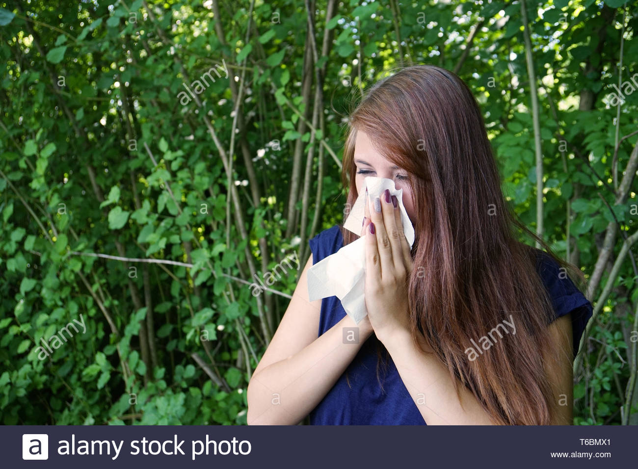 young woman blowing nose - Stock Image