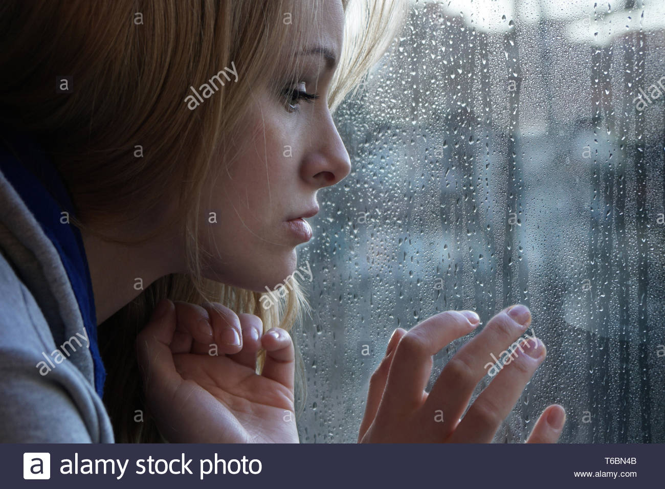 sad young woman looking through window on rainy day - Stock Image