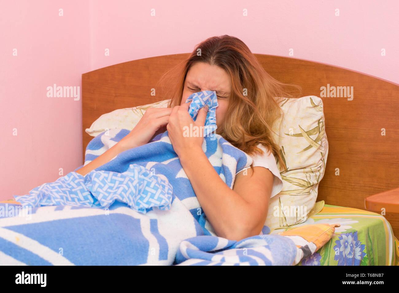 She sneezes ill with acute respiratory illness - Stock Image
