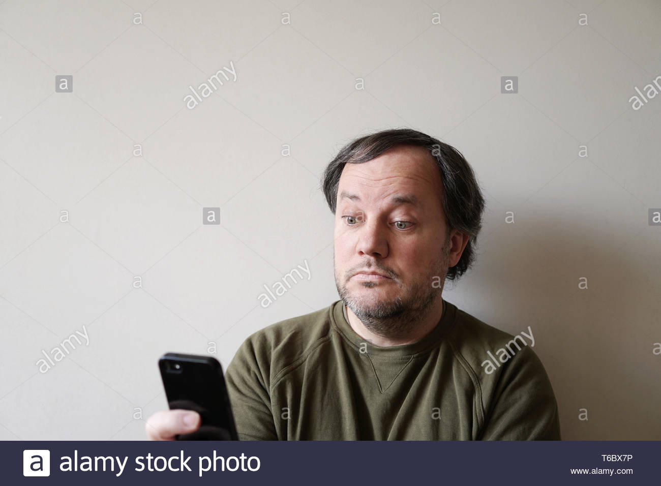 wide-eyed man looking at smartphone - Stock Image