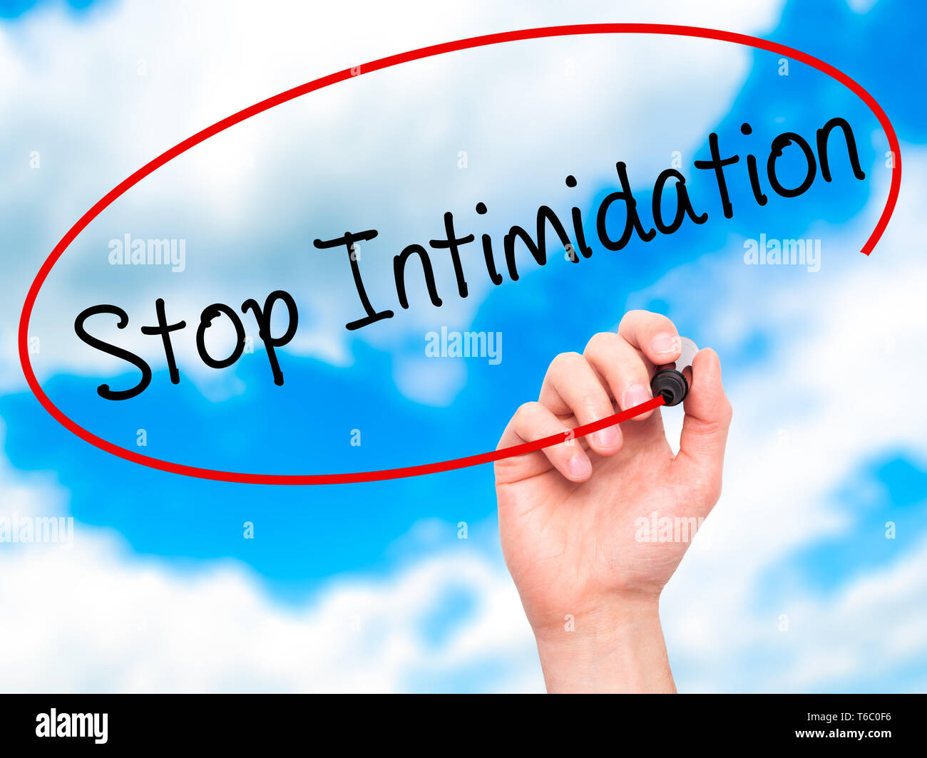 Man Hand writing Stop Intimidation with black marker on visual screen. - Stock Image