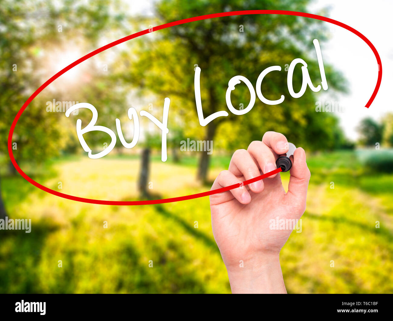 Man Hand writing Buy Local  with black marker on visual screen - Stock Image