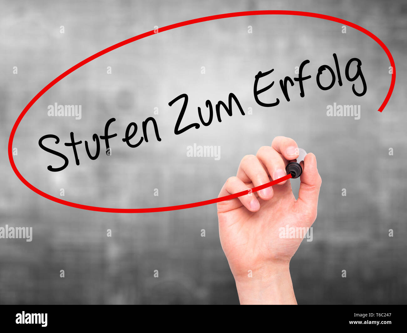 Man Hand writing Stufen Zum Erfolg (Steps to Success in German) with black marker on visual screen - Stock Image