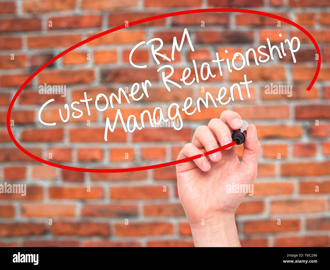 Man Hand writing CRM Customer Relationship Management  with black marker on visual screen - Stock Image