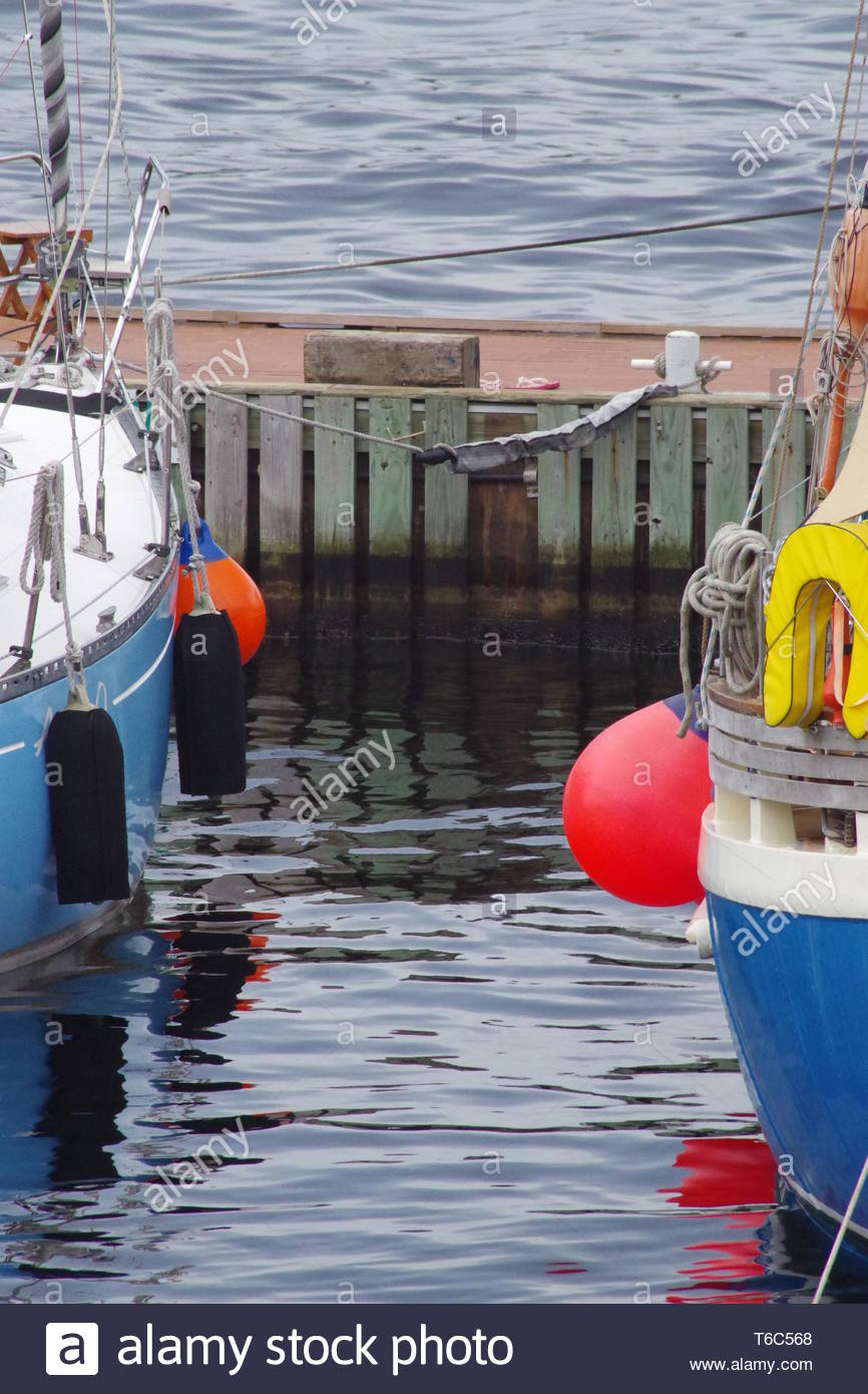 Sailing boats at the jetty with fender protection on their sides, they are ready to depart for their journey. - Stock Image