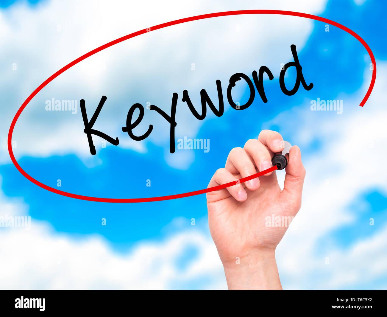 Man Hand writing Keyword with black marker on visual screen - Stock Image