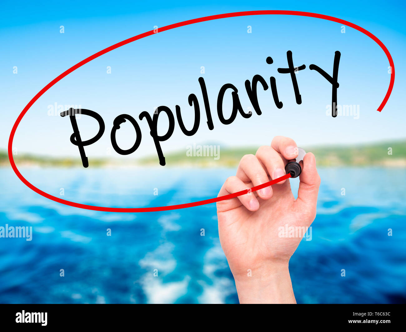 Man Hand writing Popularity with black marker on visual screen. Stock Photo