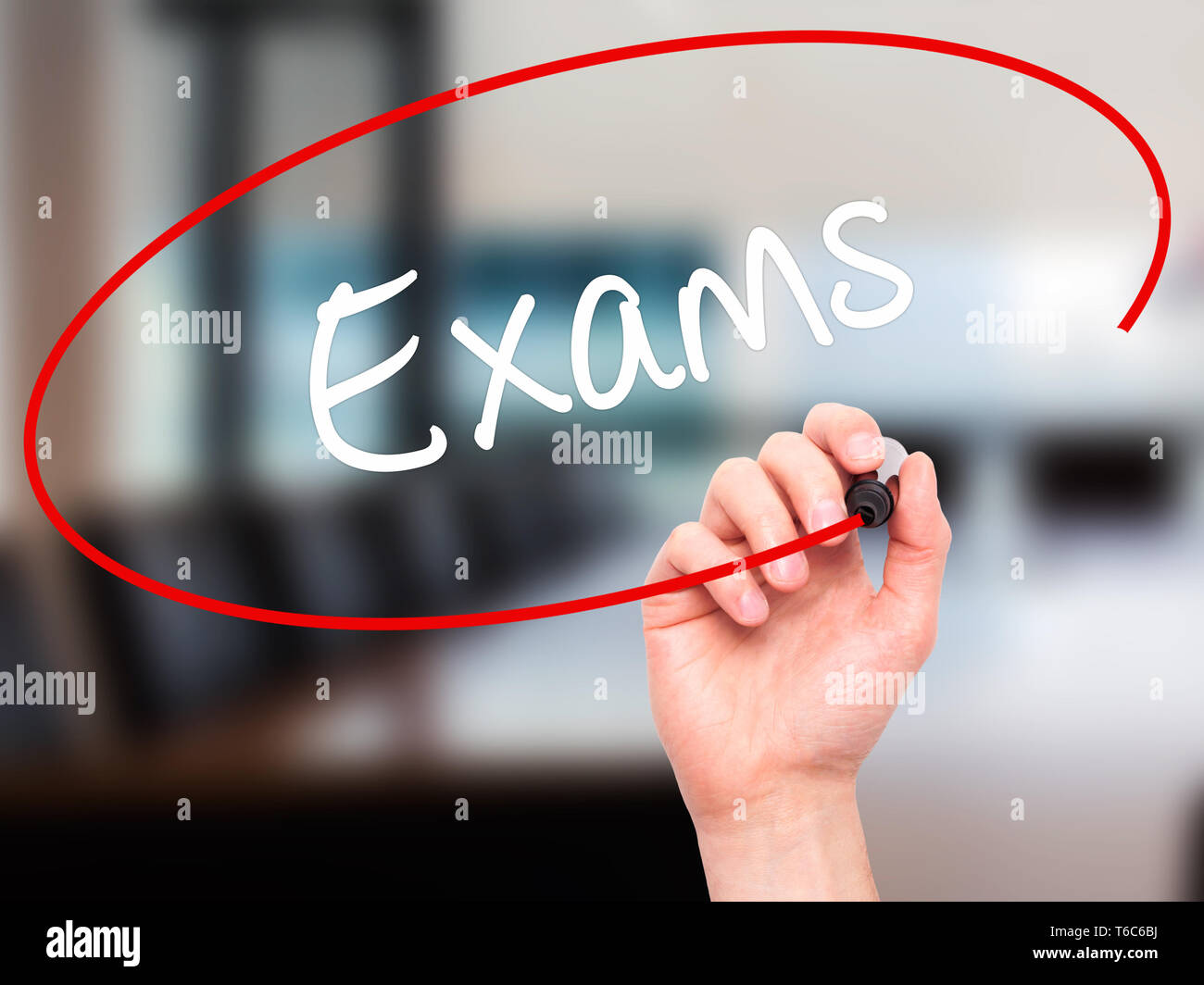 Man Hand writing Exams with black marker on visual screen - Stock Image