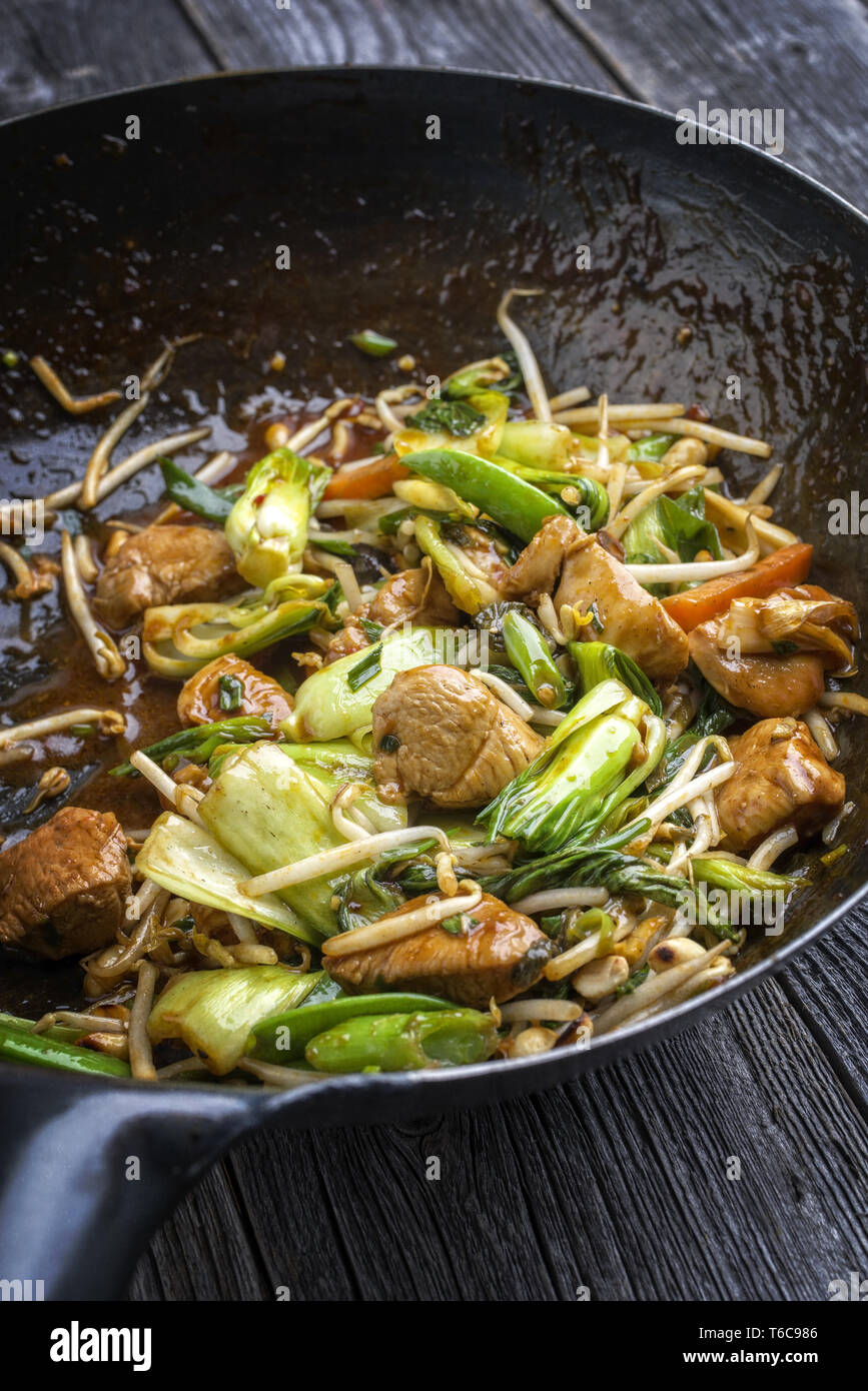 Traditional stir fried Chicken Gung Bao with Vegetable as close-up in Wok Stock Photo