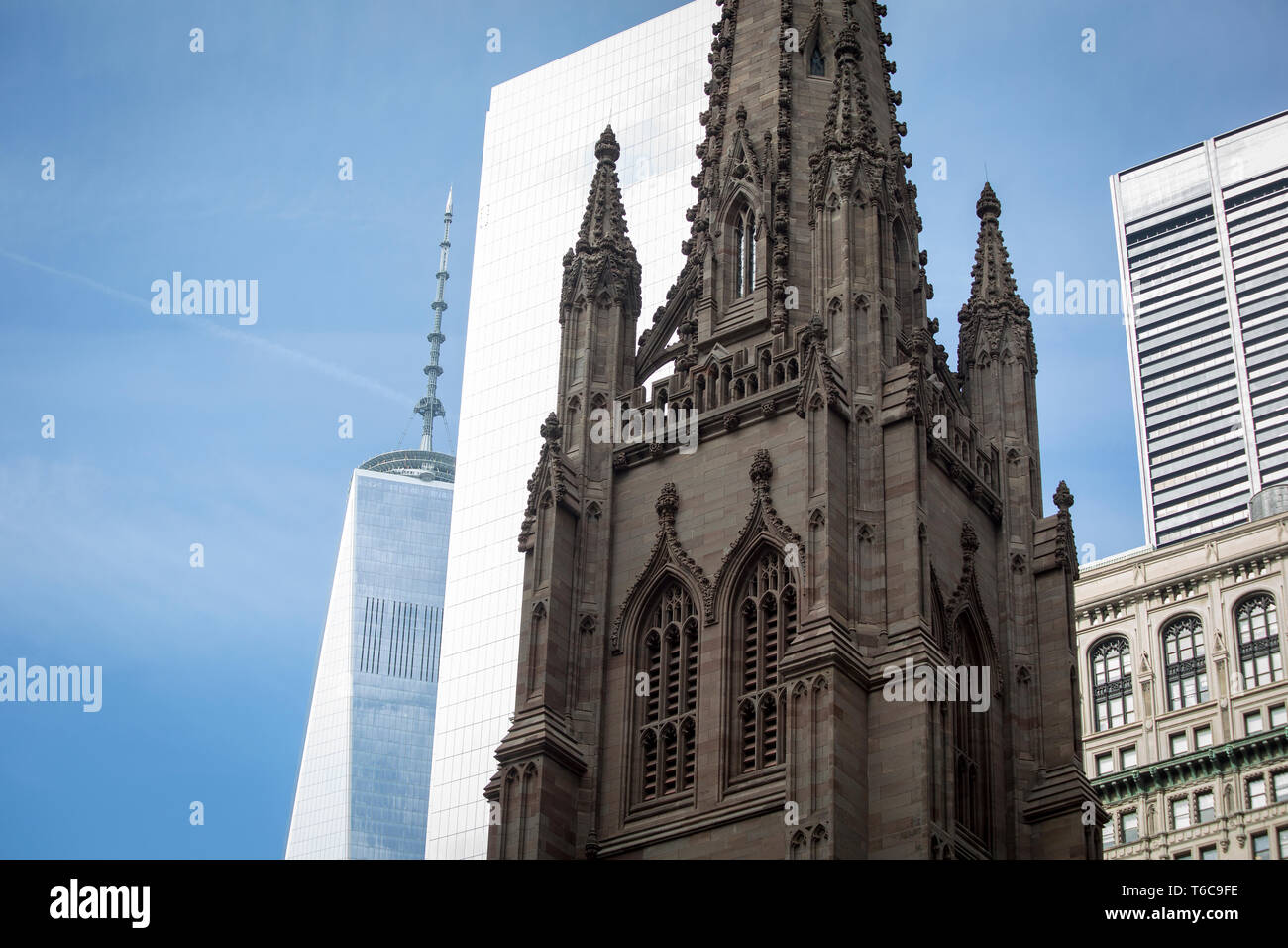 The spear of the Trinity Church. In the background is the spear of the World Trade Center 1, also known as Freedom Tower. - Stock Image