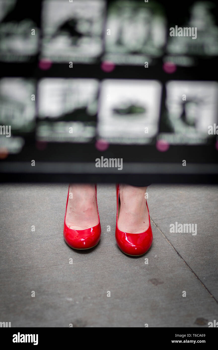 A couple of feet with red shoes are seen below a street guide of the NYSE Euronext Stock Exchange and Wall Street area. - Stock Image