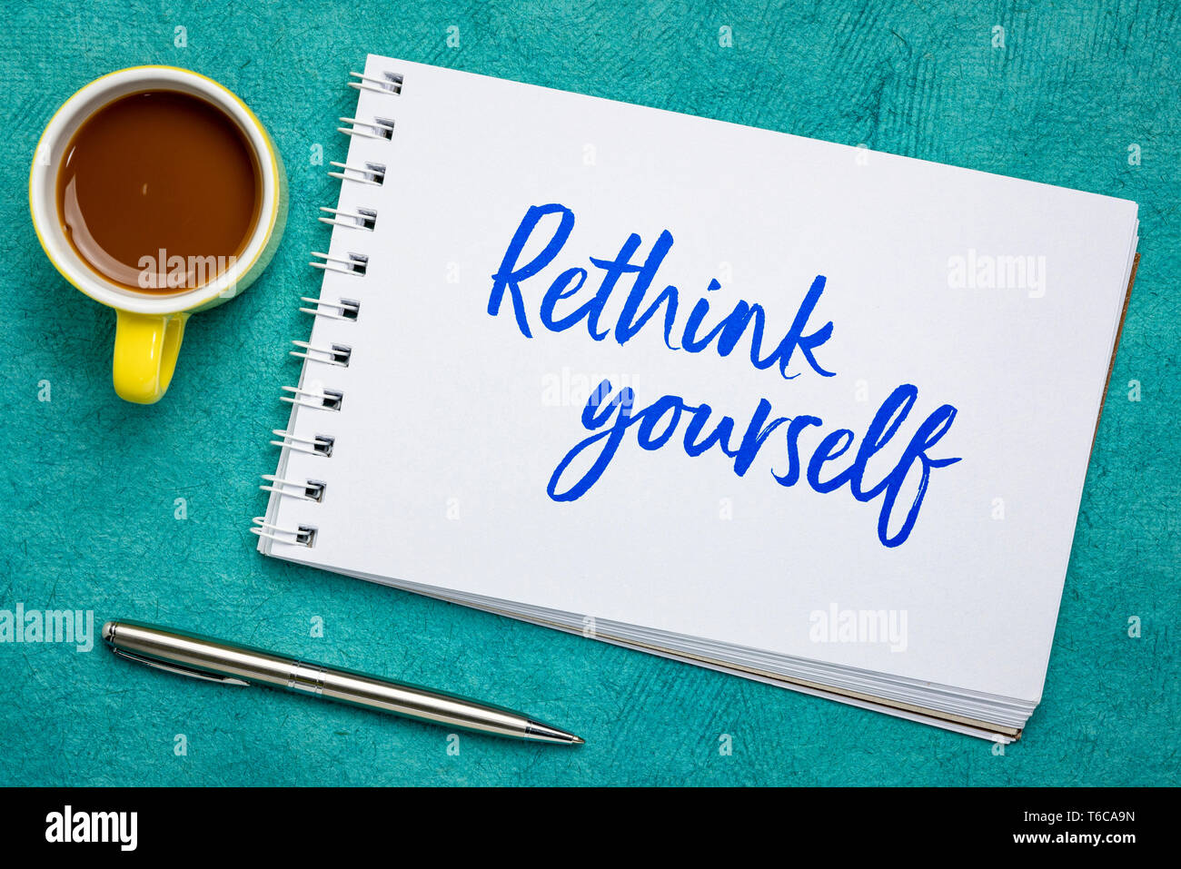 rethink yourself - advice or reminder note, handwriting in a spiral art sketchbook against against textured bark paper with a cup of coffee - Stock Image