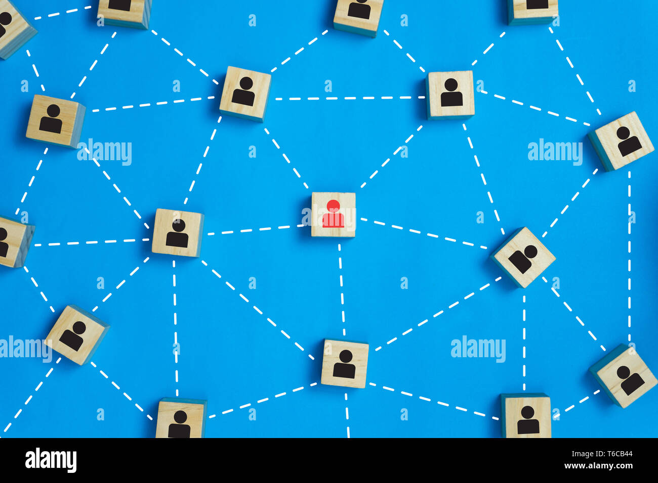 Leadership and network teamwork concepts Red businessman icon on the wooden block in the middle between the black business icon on the wooden blocks.  Stock Photo