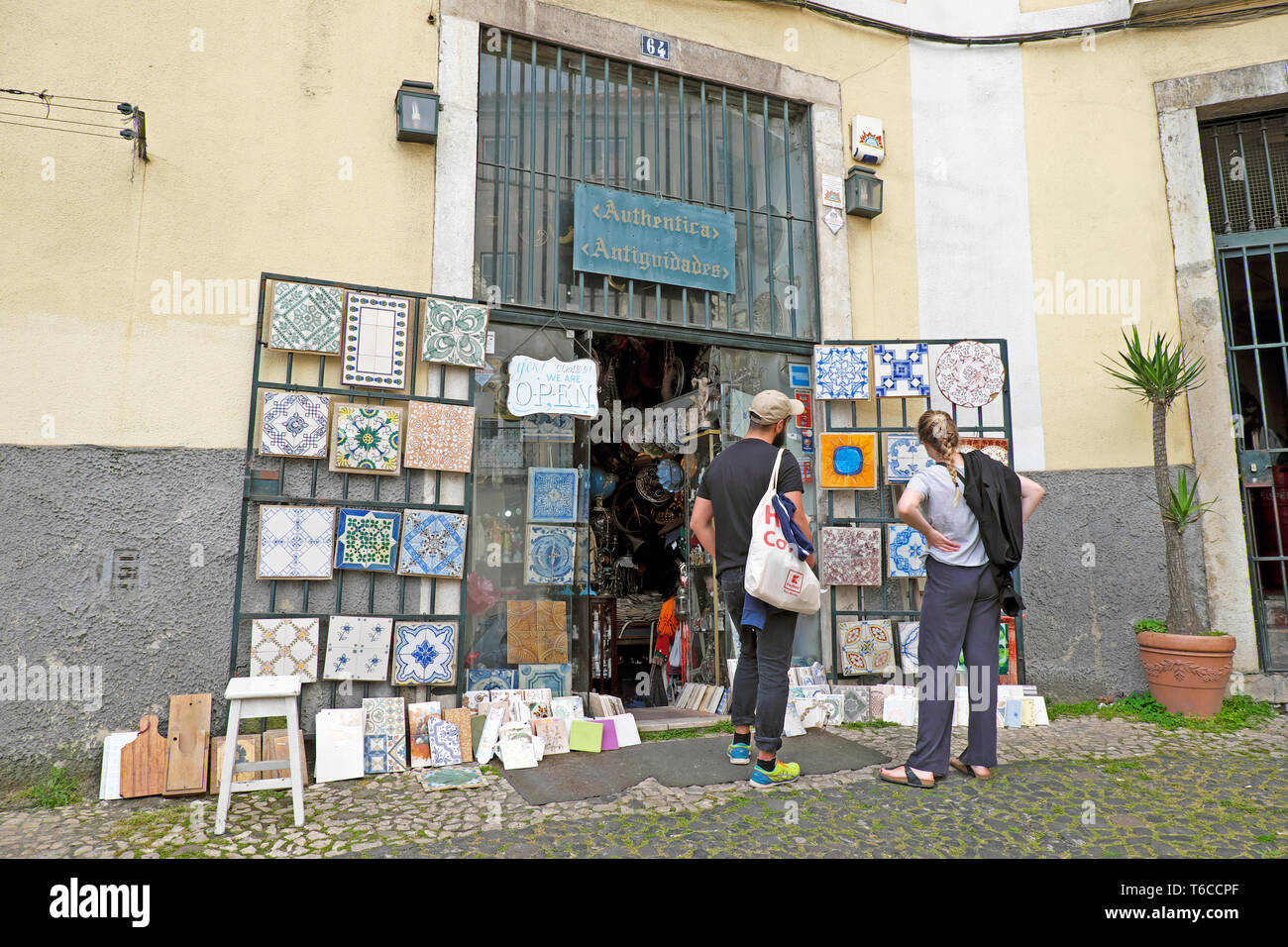 People couple looking at hand painted vintage Portuguese tiles outside an antique shop in the Alfama district of city of Lisbon Portugal  KATHY DEWITT - Stock Image