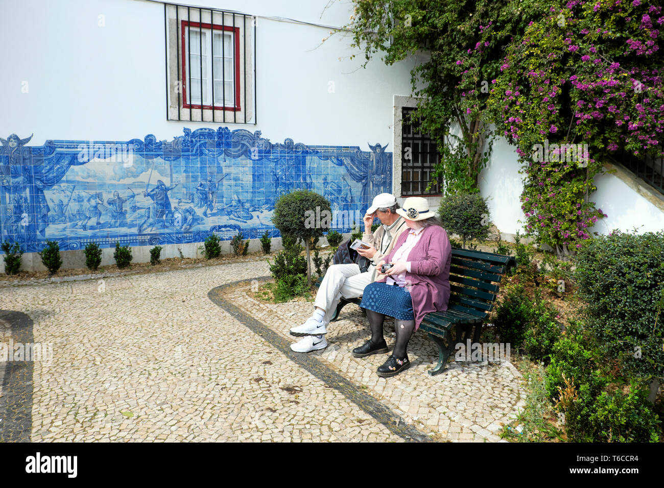 Tourists looking at a historical depiction of Seige of Lisbon 1147 commemorated in blue wall tiles azulejos in Alfama Lisboa Portugal  KATHY DEWITT Stock Photo