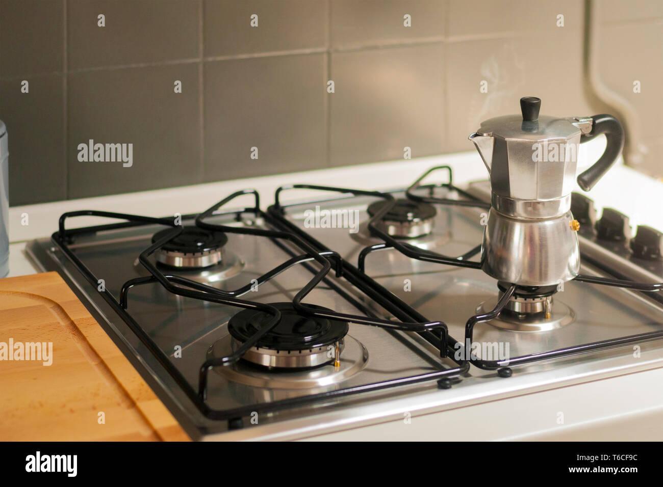 A steaming moka pot on the kitchen stove - Stock Image