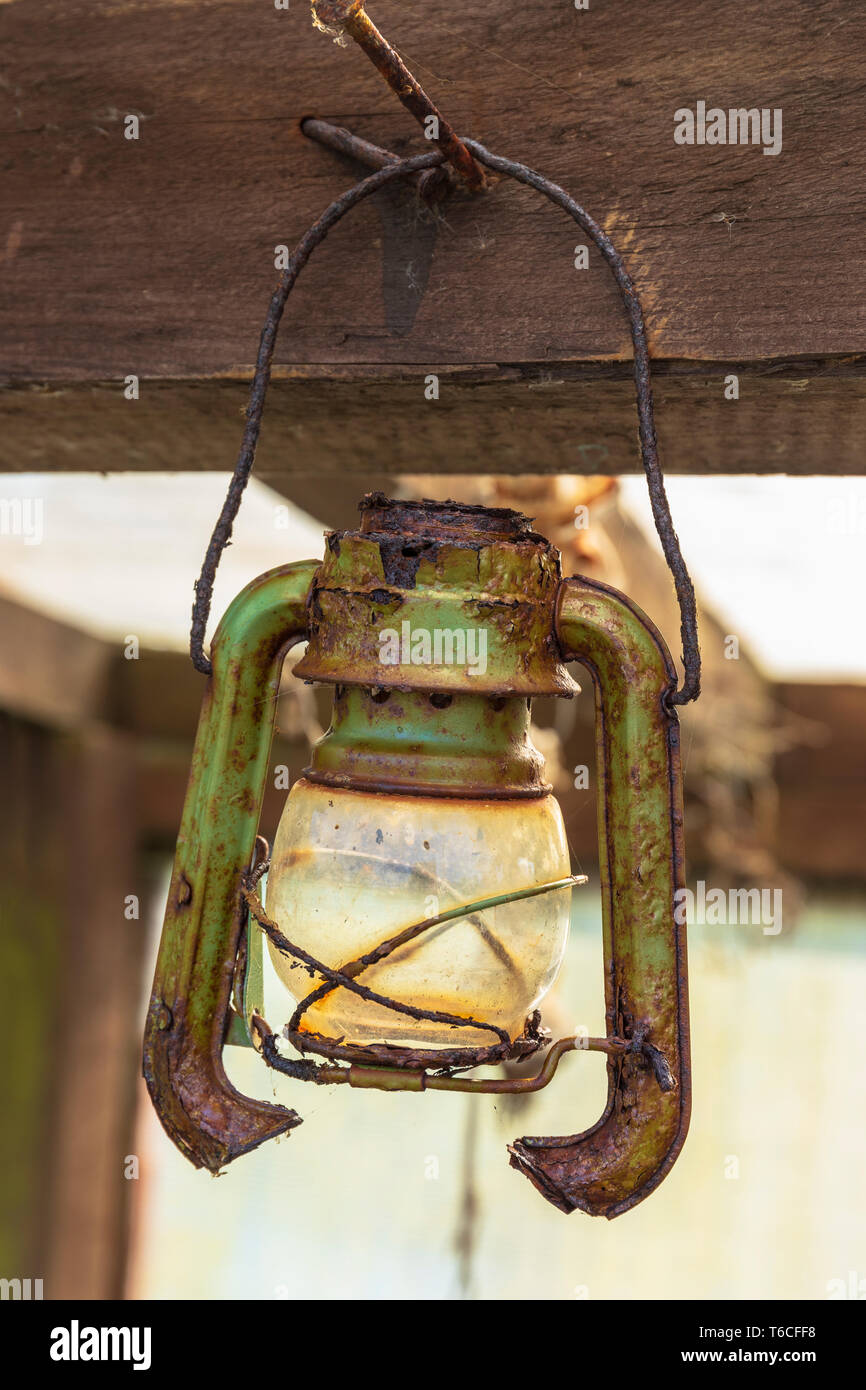 Pendant paraffin lamp, rusting and abandoned, hanging in a shed, Kilwinning, Scotland - Stock Image