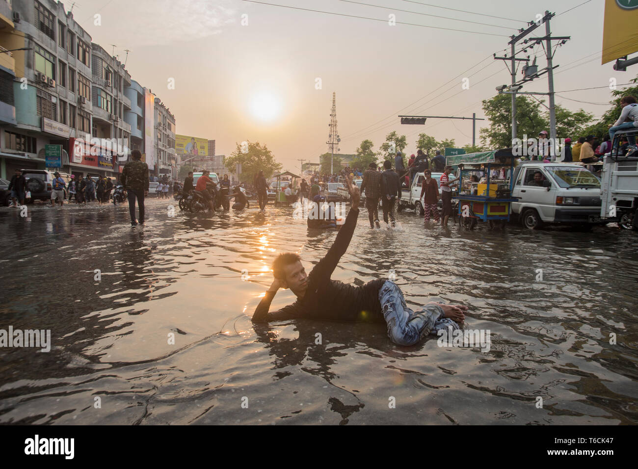 Reveller laying in a flooded street in Mandalay during the water festival of the Thingyan New Year Festival in Myanmar. - Stock Image