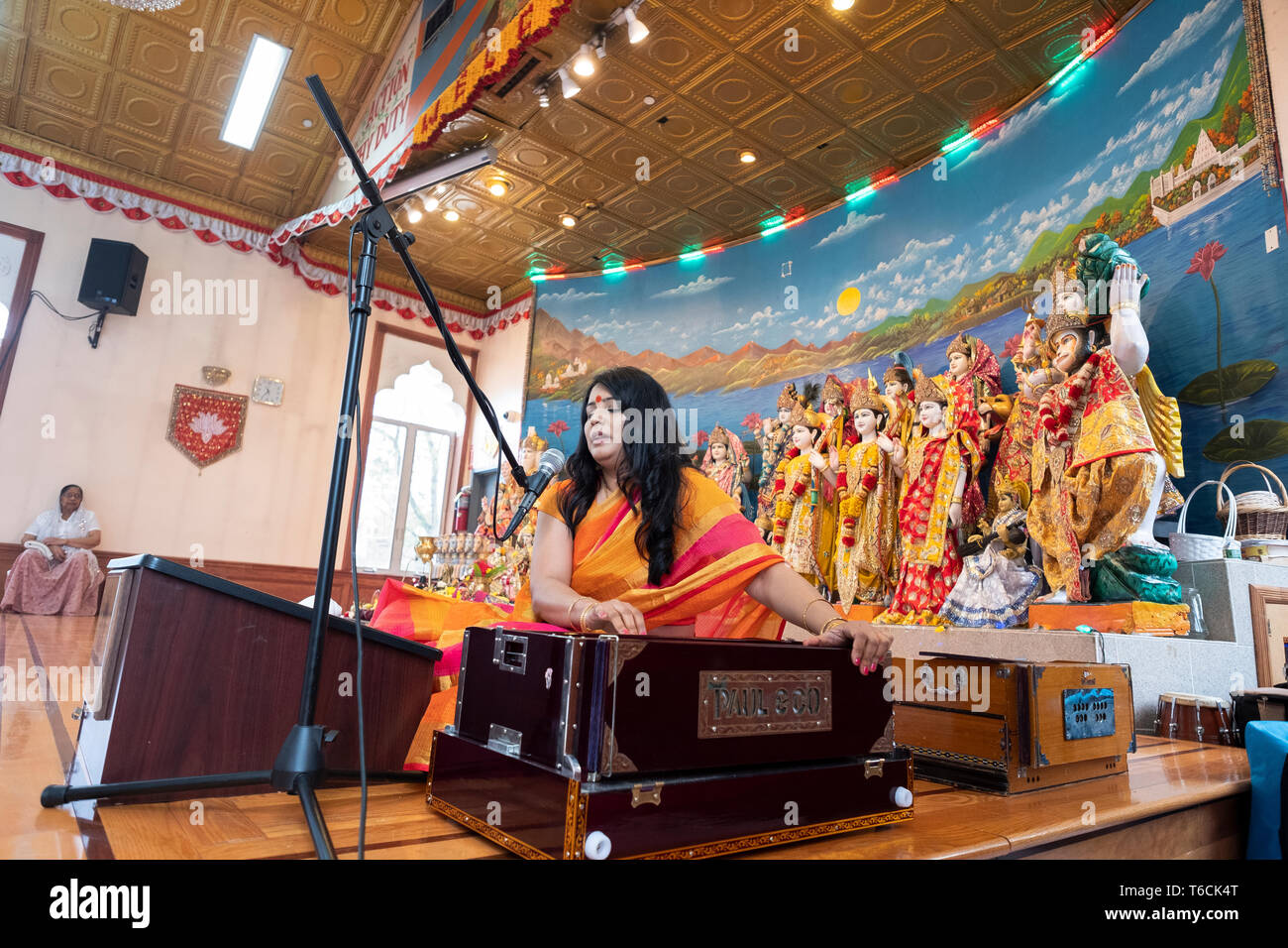 PANDITA. A female Hindu priestess sings a prayer while playing a harmonium at a temple in Jamaica, Queens, New York City. Stock Photo