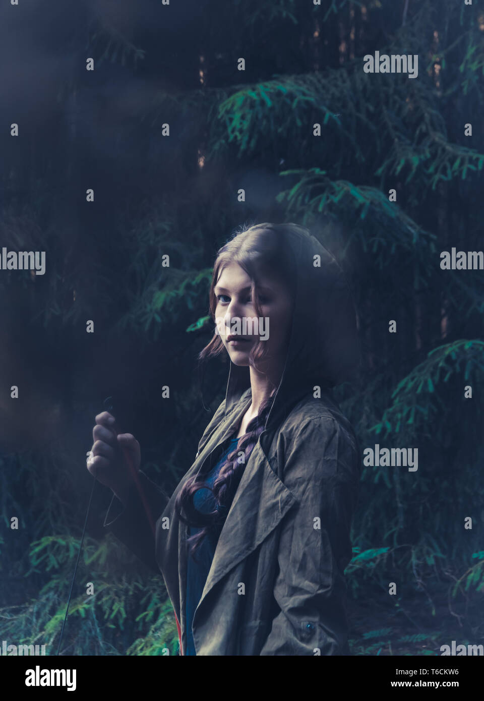Enigmatic woman stood in dark forest Stock Photo