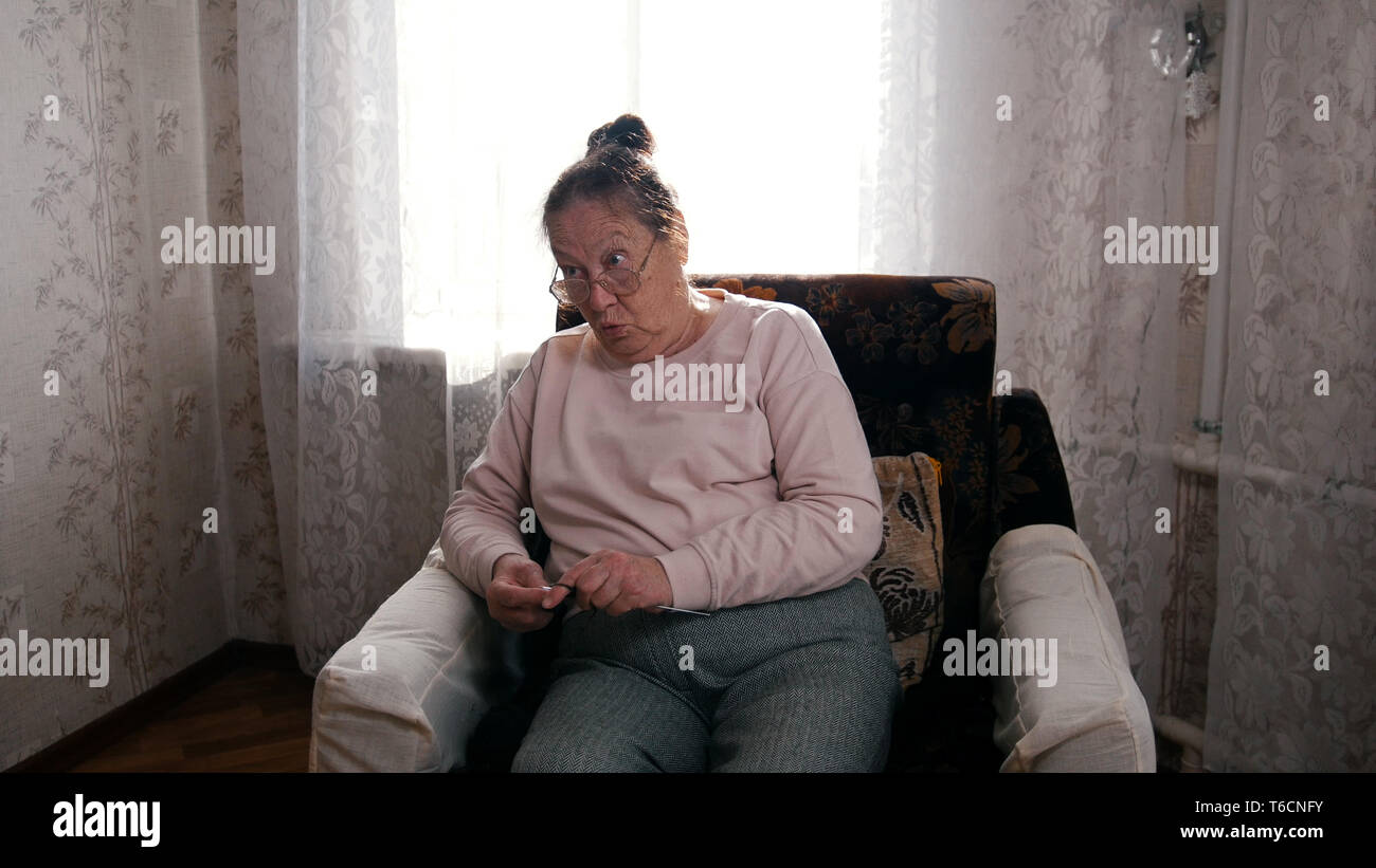 An old angry woman in glasses sitting in the armchair and knitting - Stock Image