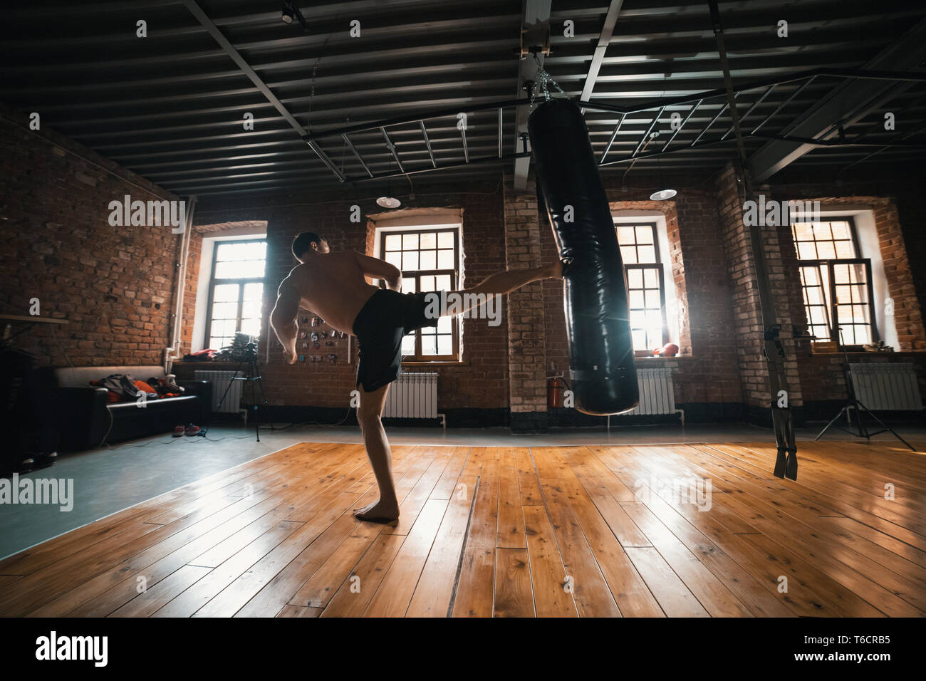 An athletic man boxer training with a punching bag in the gym. Kicking the bag with a leg - Stock Image