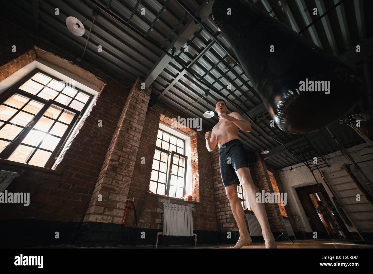 A man boxer training with a punching bag in the gym - Stock Image