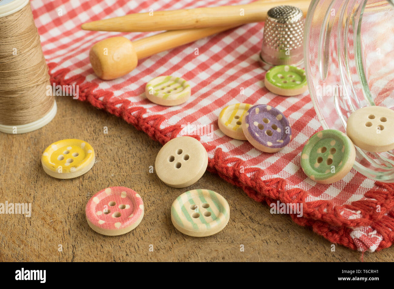 Wooden buttons with colored stripes of colors on a red and white checkered tablecloth, sewing Stock Photo