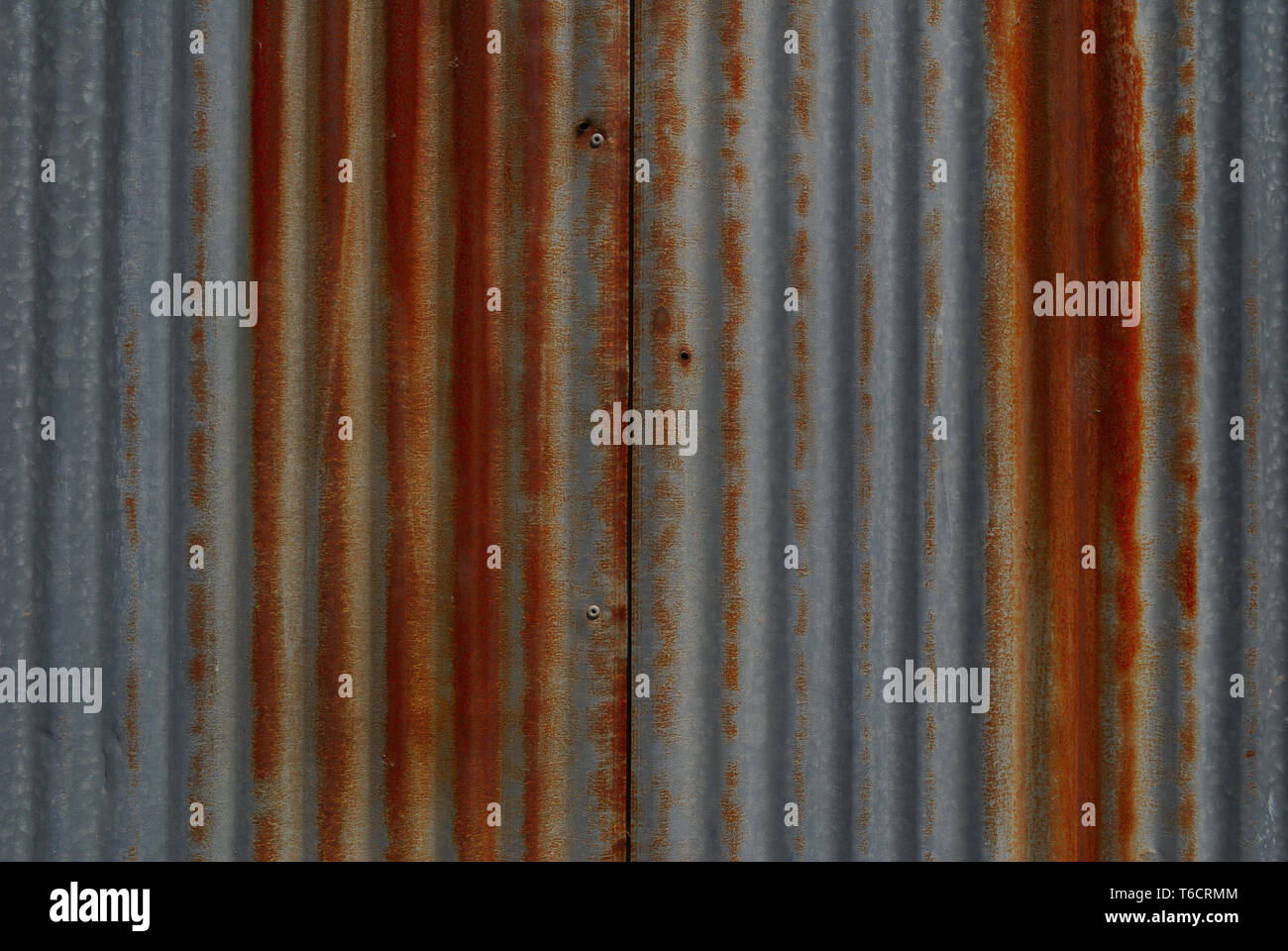 Galvanized surface that is rusty red - Stock Image