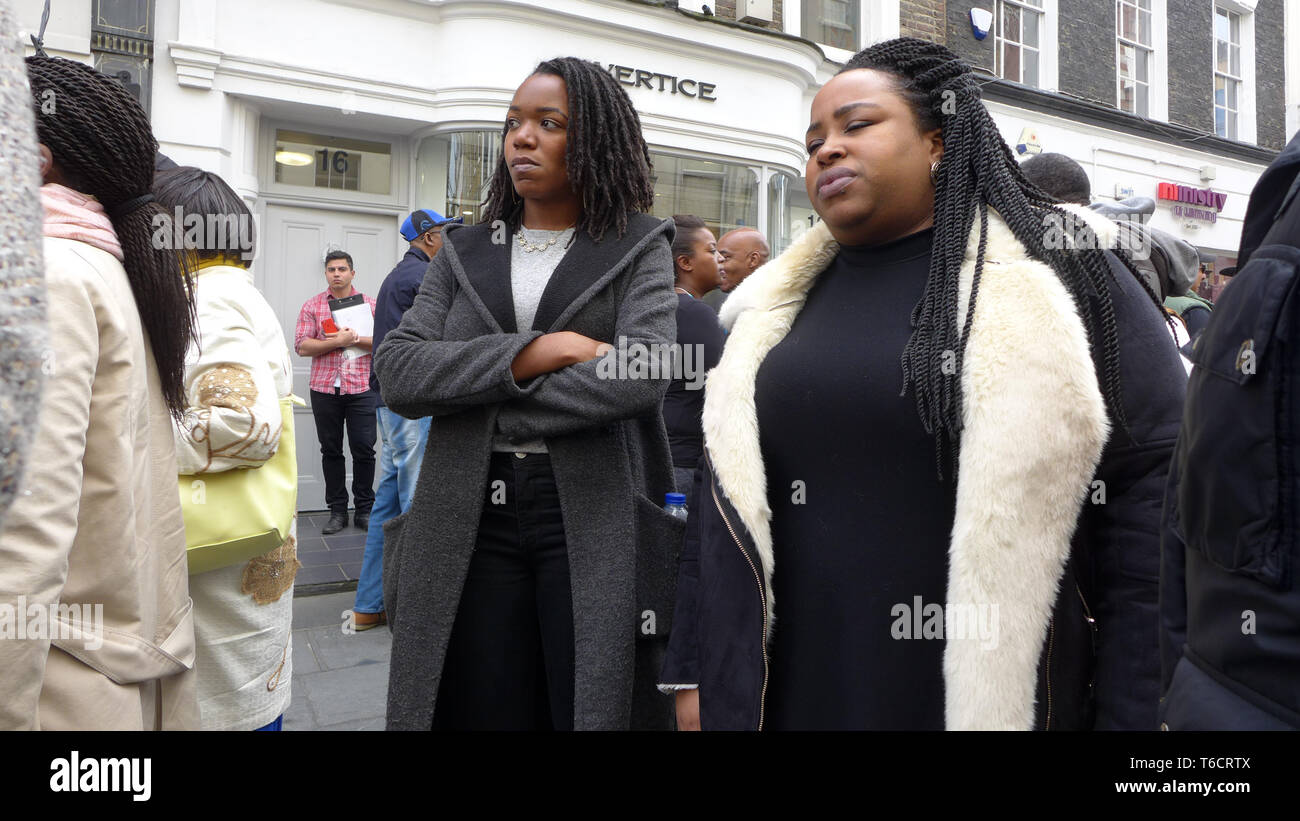 Two caribbean women standing and looking in a street event. London Stock Photo