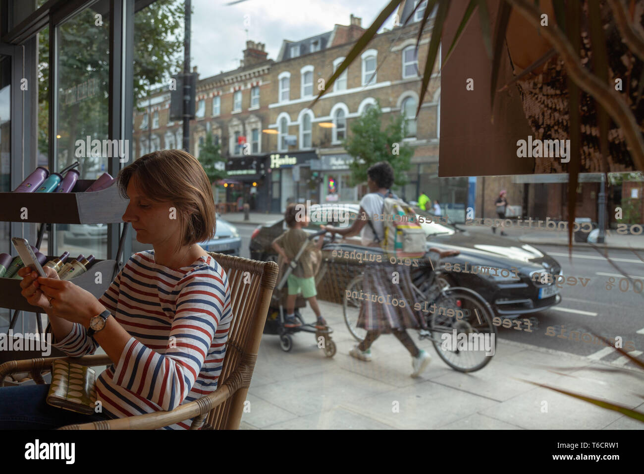 woman sitting in a hairdresser reading and passing people behind. London - Stock Image
