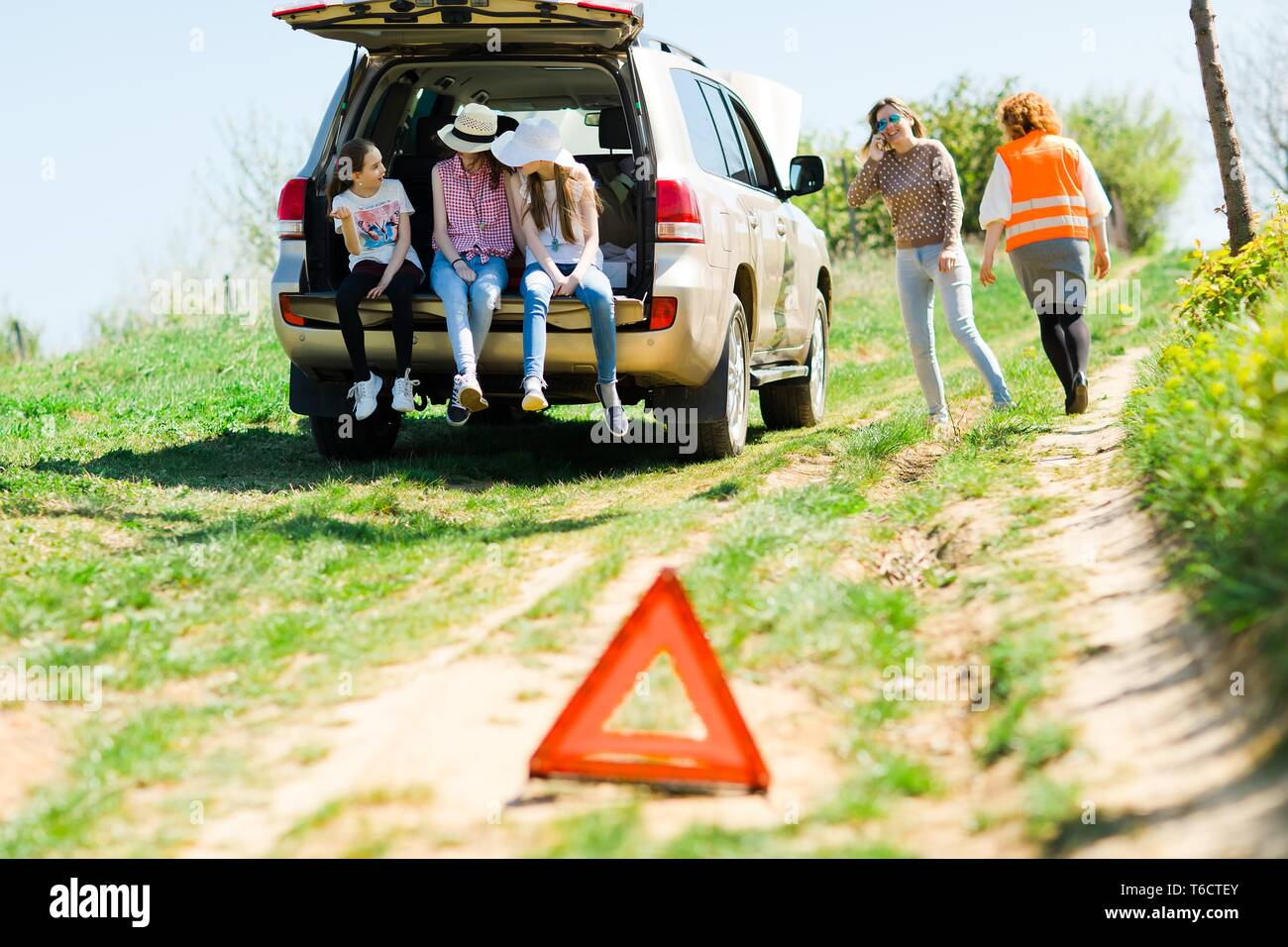 A breakdown triangle stands near a broken car - of road - family behind looking for help - Stock Image