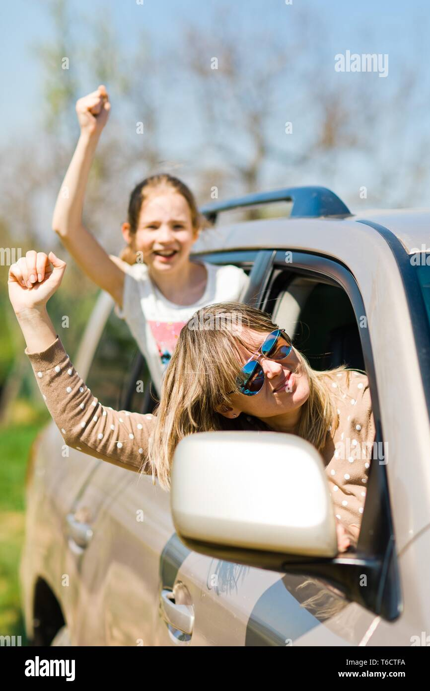 Rioters behind the wheel, female hooligans in the car showing gestures around - sport fans Stock Photo