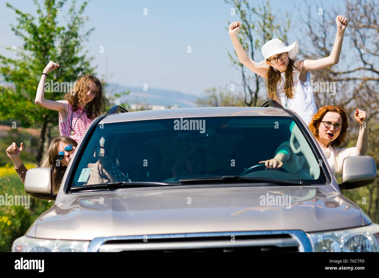 Rioters behind the wheel, female hooligans in the car showing gestures from windows Stock Photo