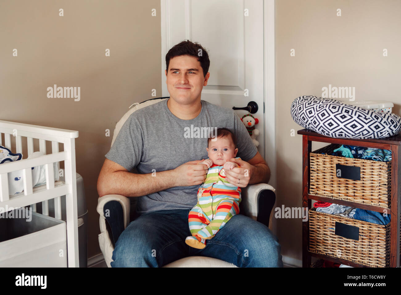 Young Caucasian father sitting in kids nursery room with newborn baby. Male man parent holding child on his hands lap. Authentic lifestyle adorable mo - Stock Image