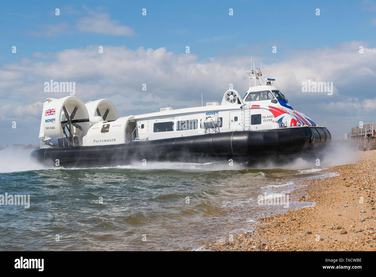 Island Flyer, a Griffon Hoverwork 12000TD hovercraft from Hovertravel on the Solent sea, landing on the beach Southsea in Hampshire, England, UK. - Stock Image