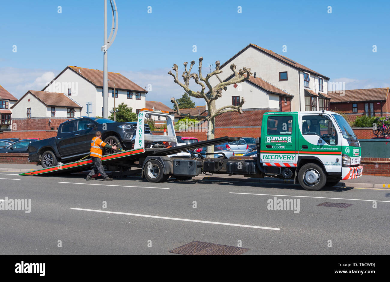 Bartletts breakdown recovery vehicle at the roadside putting a car on a trailer, in the UK. - Stock Image