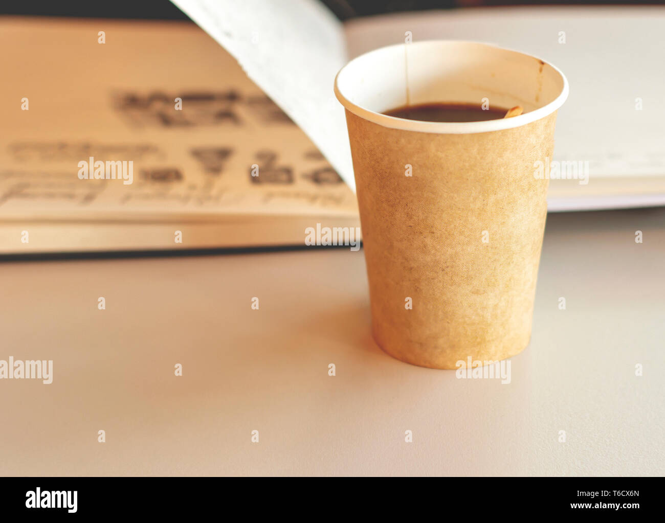 Coffee in a recyclable paper disposable glass with an open notebook in background. Relaxing break and environmental safeguard - Stock Image