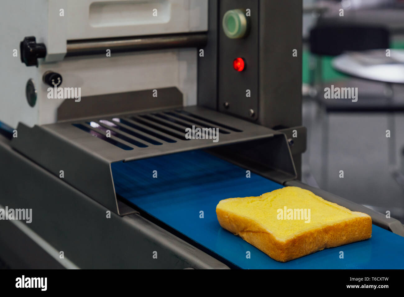 butter spread on fresh bread slice in production line on the conveyor belt of automatic bread buttering machine at bakery factory. food innovation ind - Stock Image