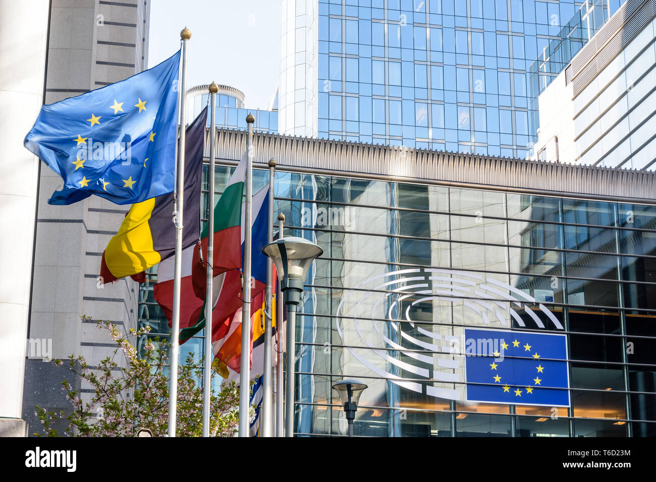 The Konstantinos Karamanlis bridge in the Espace Leopold with flags of the members of the European Union blowing in the wind in Brussels, Belgium. - Stock Image