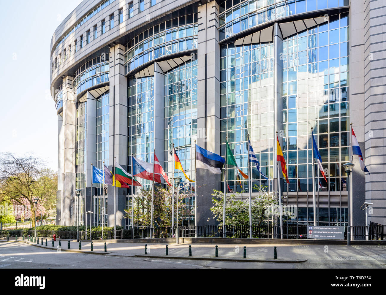 Western side of the Paul-Henri Spaak building, seat of the European Parliament hemicycle in Brussels, Belgium, with flags of member states. - Stock Image