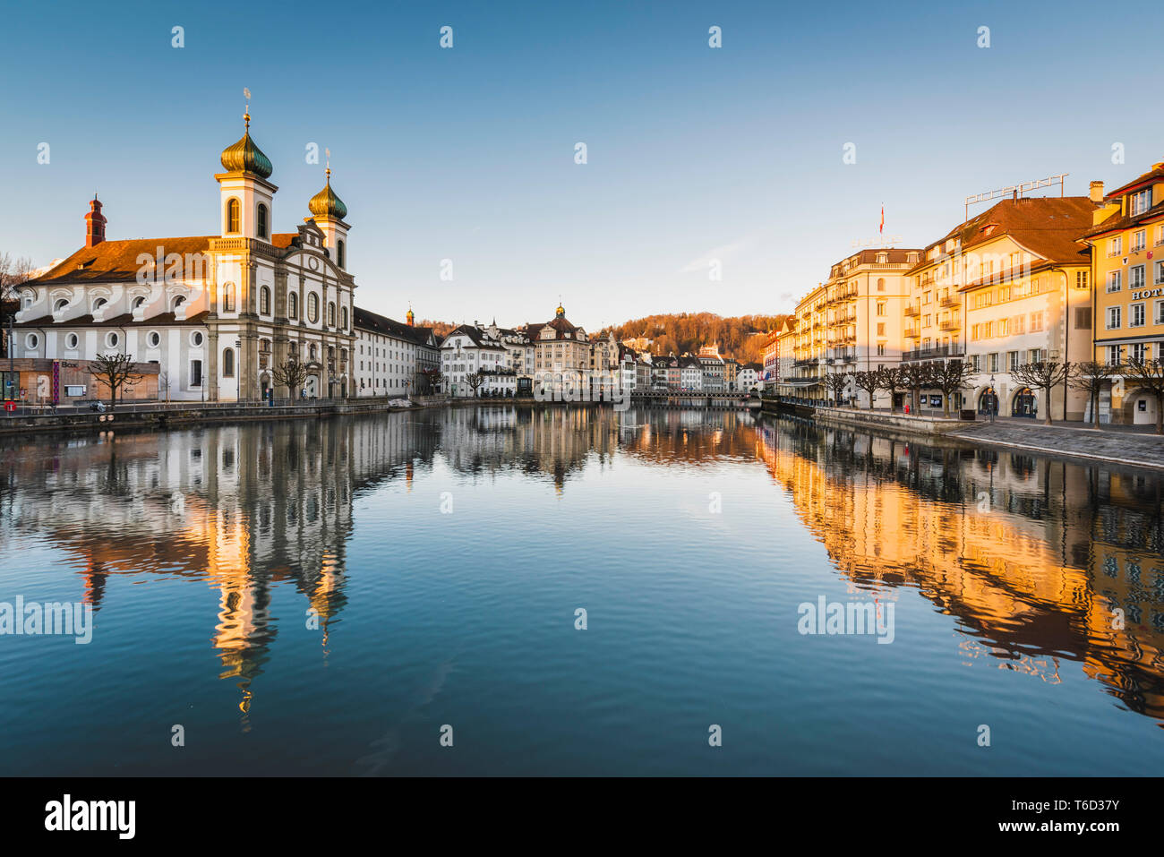 Lucerne, Switzerland. Jesuit church and Reuss river's waterfront at sunrise - Stock Image