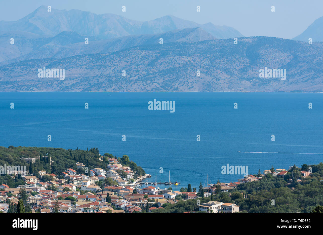 Kassiopi on the North East coast of the Greek island of Corfu in Greece with the Albanian coast in the background. - Stock Image